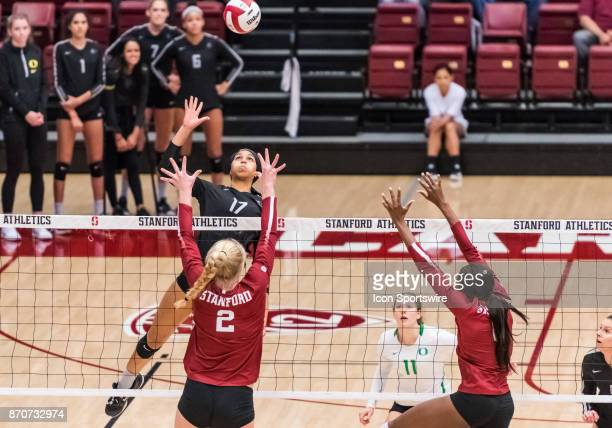 Oregon middle blocker Ronika Stone goes up for a hit with Stanford outside hitter Kathryn Plummer and Stanford middle blocker Tami Alade defending at...