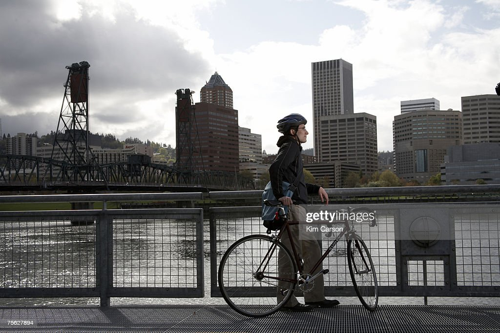 USA, Oregon, Portland, man with bicycle looking at skyline over river : Stock Photo