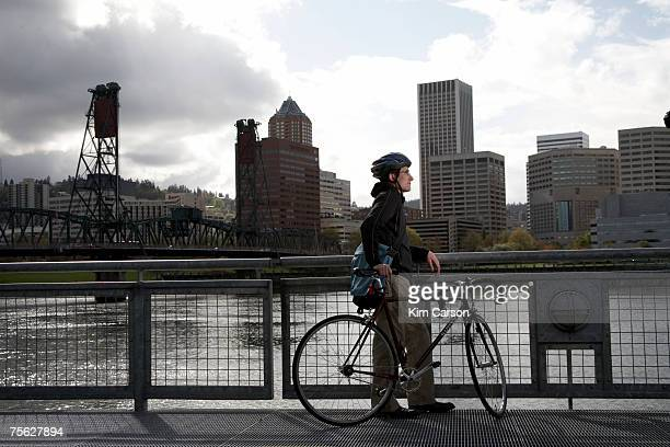 USA, Oregon, Portland, man with bicycle looking at skyline over river