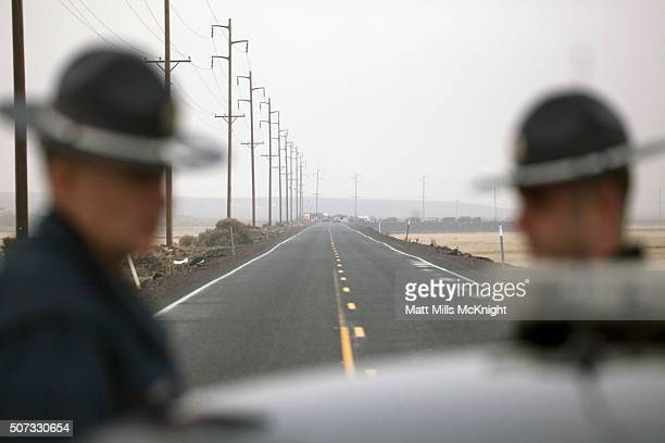 Oregon State Troopers block a road entering the Malheur National Wildlife headquarters as a large group of law enforcement officials congregate at a...