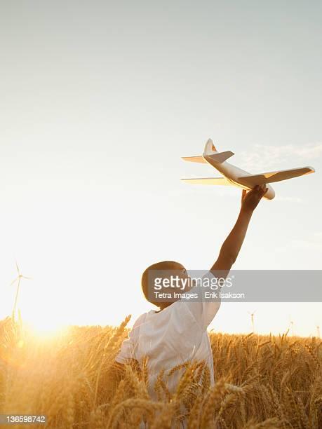 USA, Oregon, Wasco, Boy (10-11) playing with toy aeroplane in wheat field