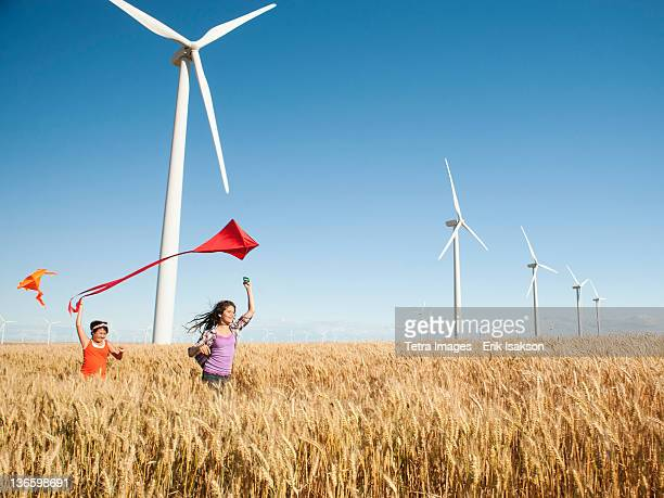 USA, Oregon, Wasco, Girls (10-11, 12-13) playing with kite in wheat field, wind turbines in background
