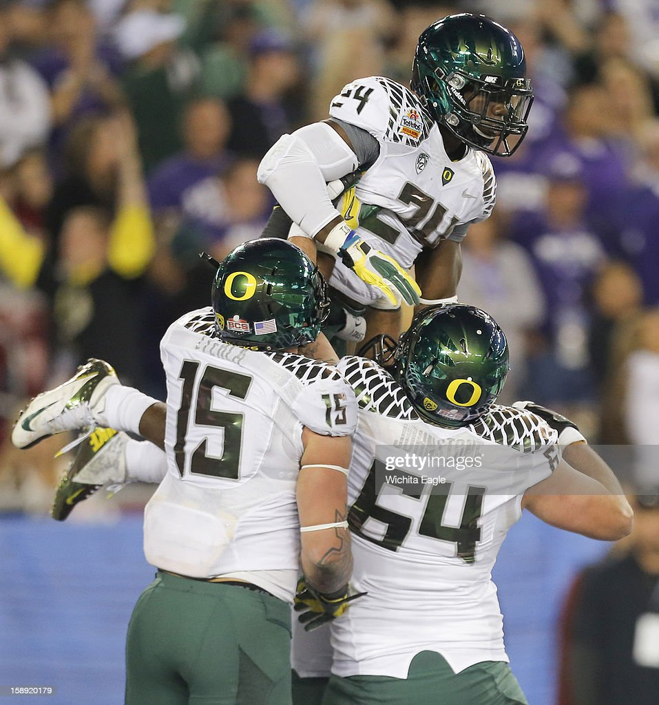 Oregon's Kenjon Barner celebrates a 24-yard touchdown pass reception with teammates Colt Lyerla (15) and Tyler Johnstone (64) during the first half against Kansas State in the Tostitos Fiesta Bowl at the University of Phoenix Stadium in Glendale, Arizona, on Thursday, January 3, 2013.