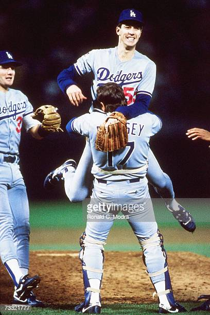 Orel Hershiser of the Los Angeles Dodgers jumps into the arms of catcher Rick Dempsey of the Los Angeles Dodgers after winning the 1988 World Series...