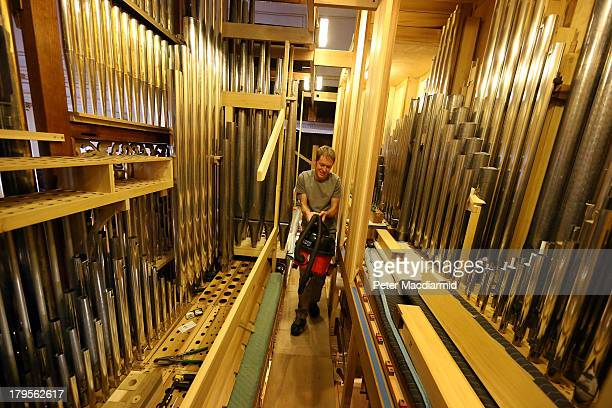 Organ builder Patrick Fischer carries a vacuum cleaner past the pipes in the organ case at St George's Church on March 19 2012 in London England The...