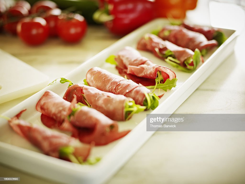Organic arugula rolled in prosciutto : Stock Photo
