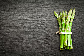 Tied up fresh organic bunch of tender asparagus shot from above on dark slate background. The bunch is placed at the right side of the frame leaving a useful copy space in the frame. DSRL studio photo