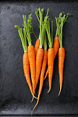 Organic carrots on black background. Food top view