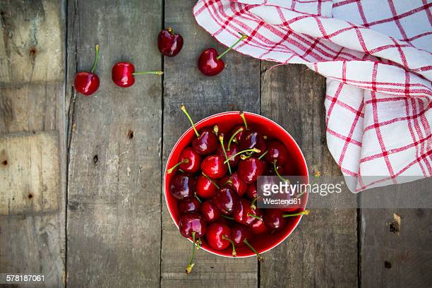 Organic cherries in bowl, kitchen towel on wood