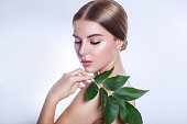 . Beautiful woman face portrait with green leaf , concept for skin care or organic cosmetics
