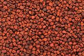 Organic dry Annatto (Bixa orellana) seeds. Macro close up background texture. Top view.