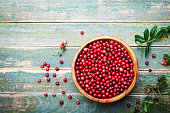 Organic fresh cowberry (lingonberry, partridgeberry, foxberry) in wooden bowl on rustic vintage table top view. Copy space for text.