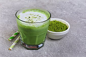 Organic green matcha tea latte in glass and powder in white bowl with cocktail straw on gray concrete background