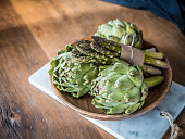Organic green vegetables food in wood bowl. Asparagus and artichoke on wooden background.