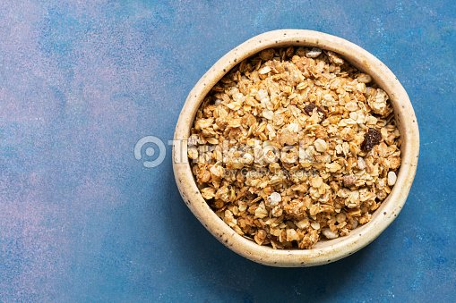 Organic homemade granola grain with oats, nuts and raisins in a clay bowl on a blue background. The view from the top, flat lay.