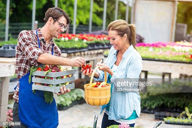 Organic local farmer giving veggies to shopper outside
