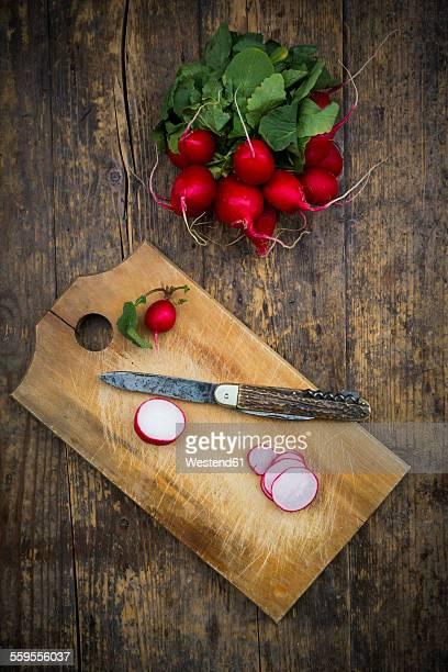 Organic radish on chopping board and pocket knife