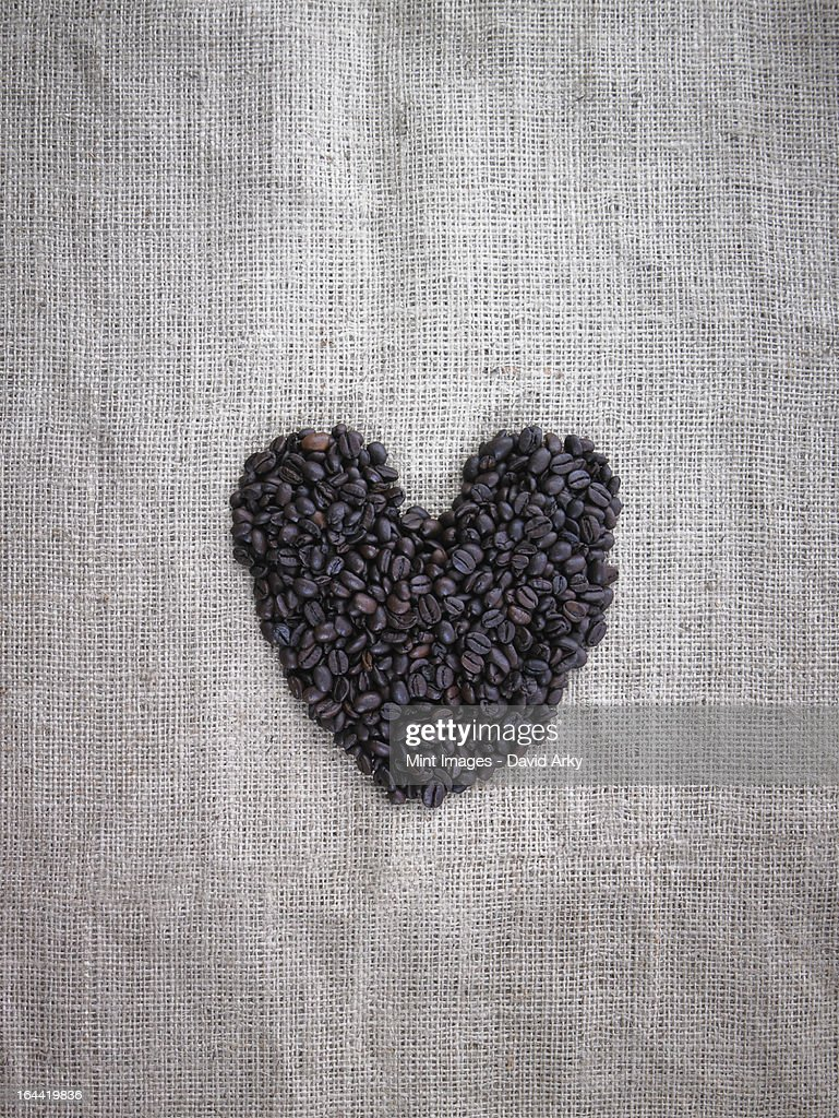 Organic roasted coffee beans in a heart shape on a burlap sack.