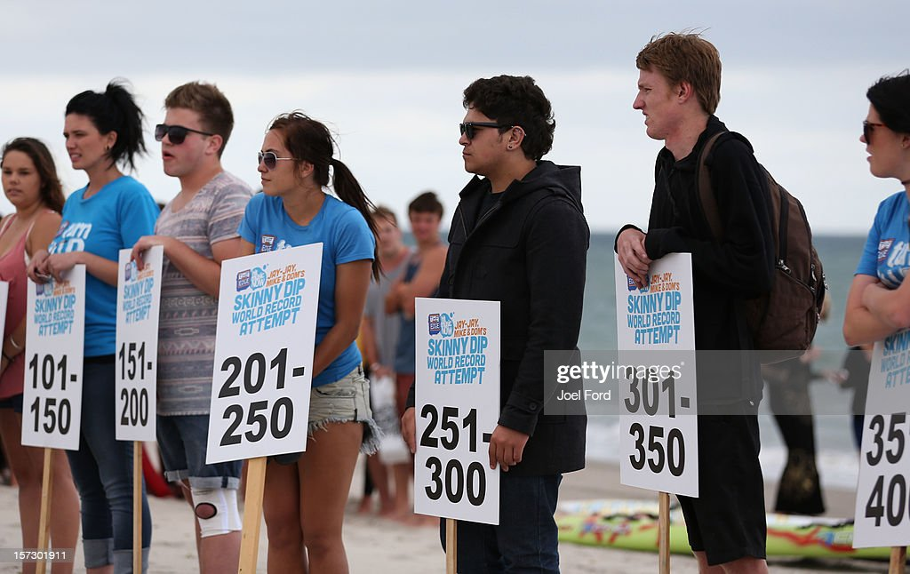 Organizers hold placards representing the numbers needed to break the skinny dip world record at Papamoa Beach on December 2, 2012 in Tauranga, New Zealand.