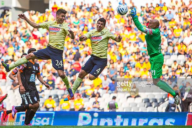 Oribe Peralta and Erick Pimentel of America fights for the ball with Oscar Perez of Pachuca during a match between America and Pachuca as part of 9th...