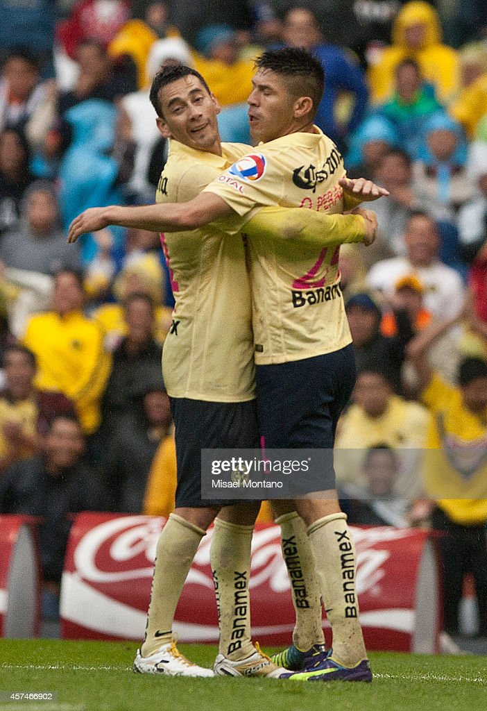 Oribe Peralta of America celebrates with Rubens Sambueza after scoring the second goal of his team during a match between America and Monterrey as part of 13th round Apertura 2014 Liga MX at Azteca Stadium on October 18, 2014 in Mexico City, Mexico.