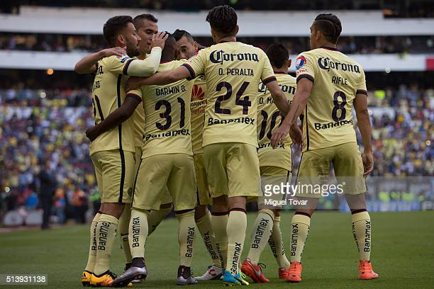 Oribe Peralta of America celebrates with teammates after scoring the first goal of his team during the 9th round match between America and Morelia as...