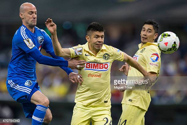 Oribe Peralta of America fights for the ball with Laurent Ciman of Montreal Impact during a Championship first leg match between America and Montreal...