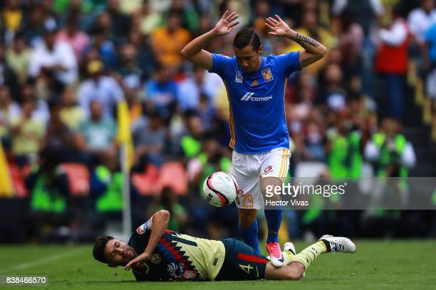 Oribe Peralta of America struggles for the ball with Jesus Dueñas of Tigres during the 6th round match between America and Tigres UANL as part of the...