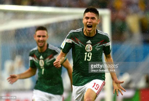 Oribe Peralta of Mexico celebrates after scoring a goal during the 2014 FIFA World Cup Brazil Group A match between Mexico and Cameroon at Estadio...