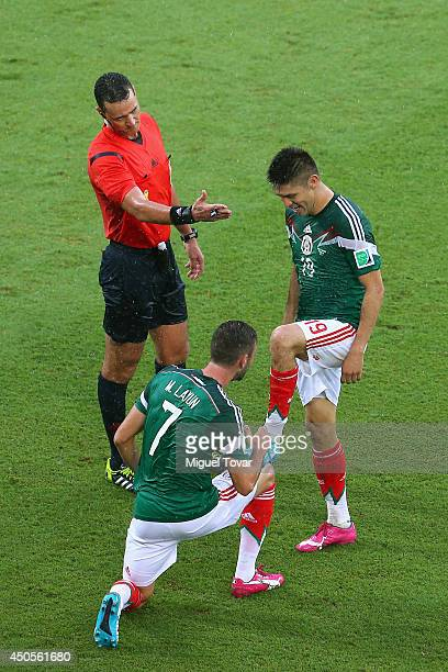 Oribe Peralta of Mexico celebrates his goal with teammate Miguel Layun as referee Wilmar Roldan gestures during the 2014 FIFA World Cup Brazil Group...