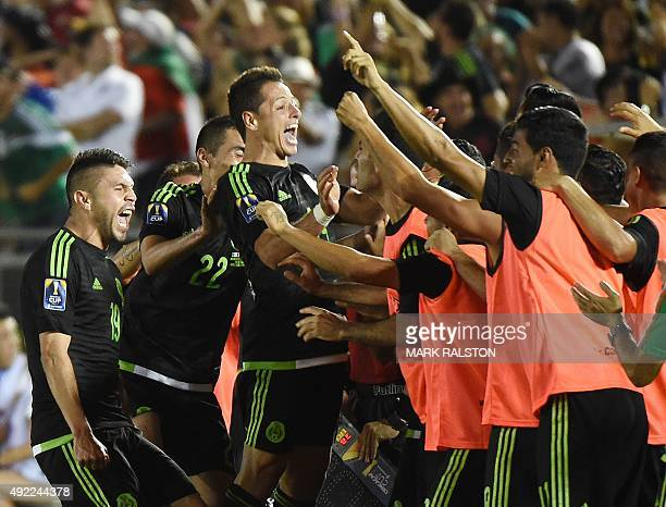 Oribe Peralta of Mexico celebrates with teammates Paul Aguilar and Javier Hernández after scoring a goal during their 2015 CONCACAF Cup game against...