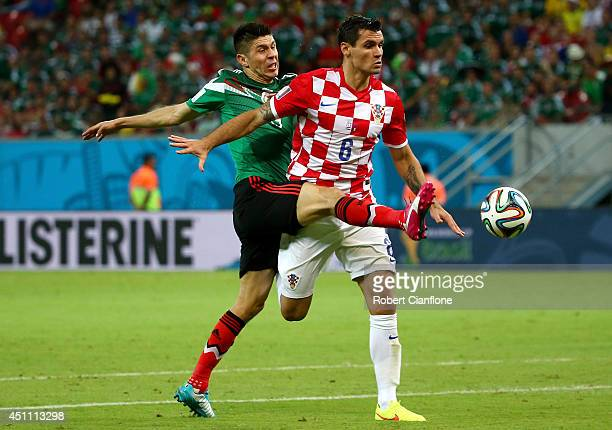 Oribe Peralta of Mexico challenges Dejan Lovren of Croatia during the 2014 FIFA World Cup Brazil Group A match between Croatia and Mexico at Arena...
