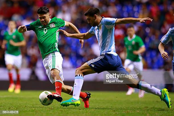 Oribe Peralta of Mexico fights for the ball with Lisandro Magallan of Argentina during an U23 International Friendly between Mexico and Argentina at...