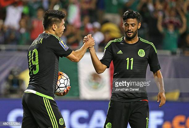 Oribe Peralta of Mexico is congratulated by teammate Carlos Vela after scoring a first half goal against Cuba during a match in the 2015 CONCACAF...
