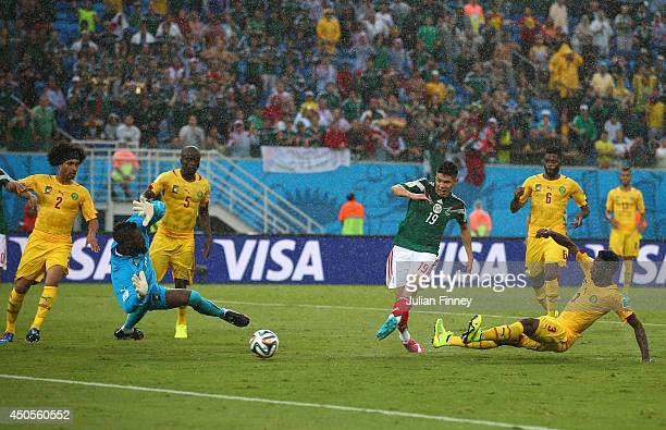 Oribe Peralta of Mexico shoots and scores a goal past Charles Itandje of Cameroon in the second half during the 2014 FIFA World Cup Brazil Group A...
