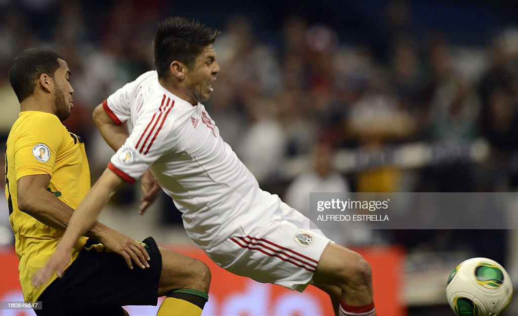 Oribe Peralta (R) of Mexico vies for the ball with Adrian Mariappa (L) of Jamaica during their Brazil-2014 FIFA World Cup CONCACAF football qualifier at Azteca Stadium in Mexico City, on February 6, 2013. AFP PHOTO/Alfredo Estrella