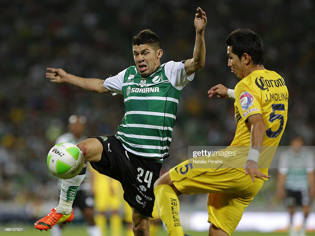 <a gi-track='captionPersonalityLinkClicked' href=/galleries/search?phrase=Oribe+Peralta&family=editorial&specificpeople=2496229 ng-click='$event.stopPropagation()'>Oribe Peralta</a> of Santos and Jesus Molina of America fight for the ball during the Quarterfinal second leg match between Santos Laguna and America as part of the Clausura 2014 Liga MX Playoffs at Corona Stadium on May 03, 2014 in Torreon, Mexico.