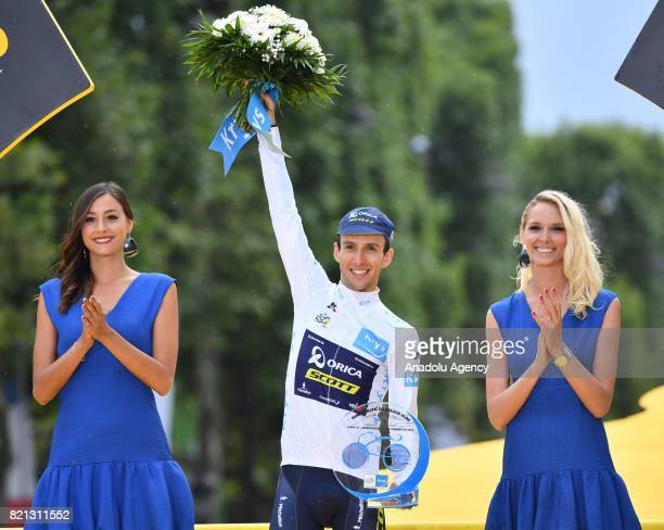 Orica Scott team rider Simon Yates of Great Britain celebrates as the best young rider on the podium after the Tour de France 2017 cycling race at...