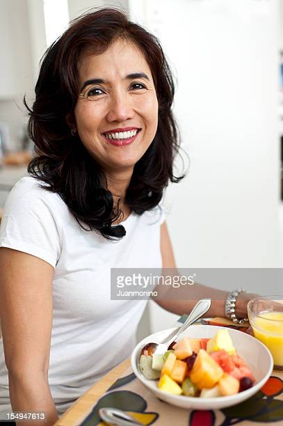 Oriental Housewife Having Fruit for Breakfast
