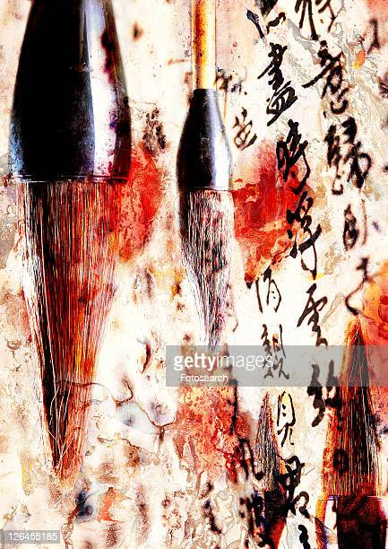 Oriental text superimposed on wet paint brushes