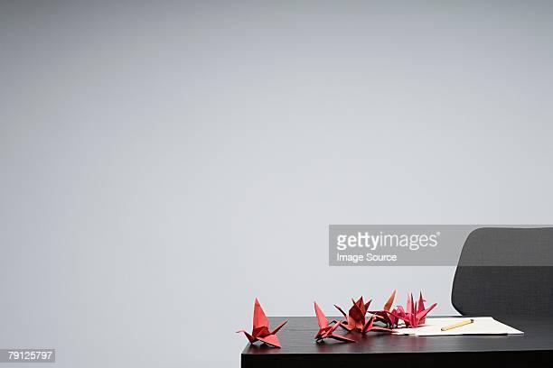 Origami Vögel in einer Reihe auf einem Schreibtisch
