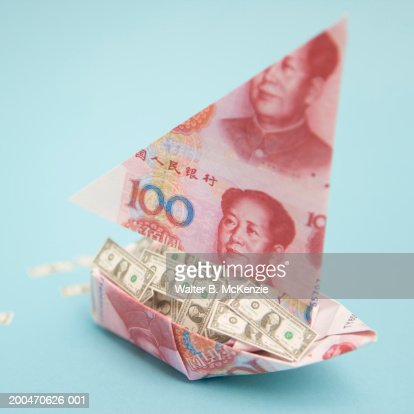 Origami boat made of Chinese currency, US Dollars in boat