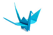 Traditional Japanese origami crane made from blue paper over white background