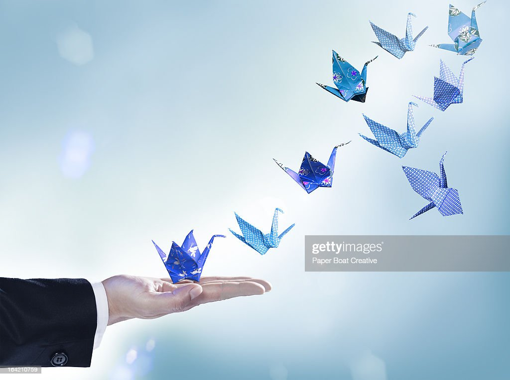 Origami cranes flying away from man's hand