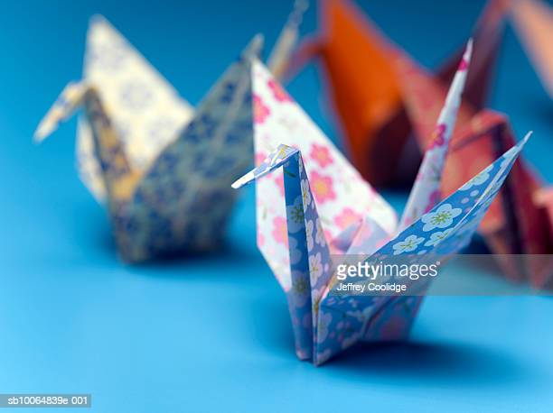 Origami cranes made from flower patterned paper, close-up (focus on foreground)