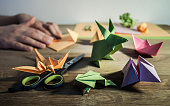 A few origami figurines on the wooden table, in the background hands folding colored paper.