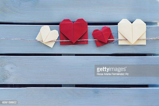 Origami heart bookmark hanging on blue wooden background. Subject captured againt soft window lighting on a blue wooden background. Overhead and copy space.