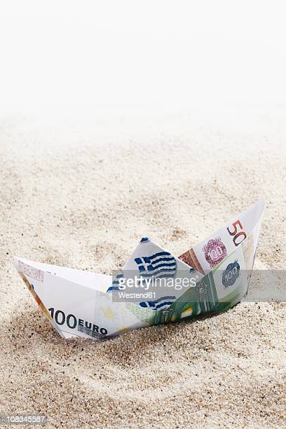 Origami paper boat of euro notes on sand
