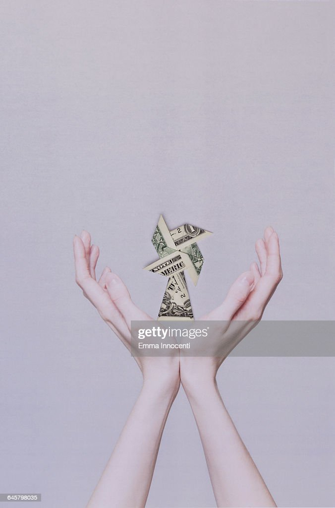 Origami windmill in hands : Stock Photo