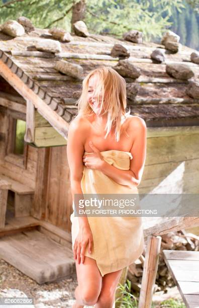 original wooden outdoor sauna hut with rocks on the roof - sensual woman in her 30s with blonde hair wearing a towel only walking up on stone steps and wooden handrail